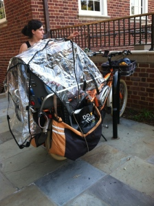 "Megan from Kidical Mass D.C. shows off her Yuba cargo bike, with two kids seats, ""monkey bars,"" panniers, and a rain cover."