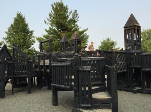The playground at the Commons. Towers and climbing structures with a castle theme painted black.