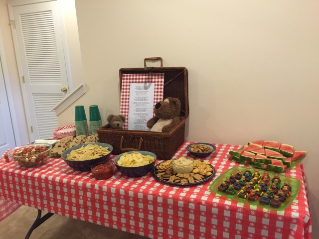 Table with picnic food and picnic basket with framed poem
