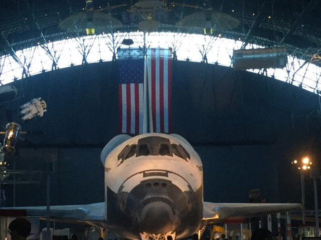Front on photo of the Space Shuttle Discovery in front of an American flag