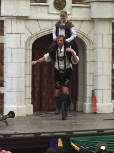 Photo of a performer on a unicycle with a boy on his back