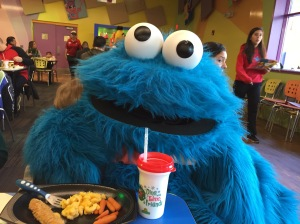Cookie Monster hugging toddler at Sesame Place