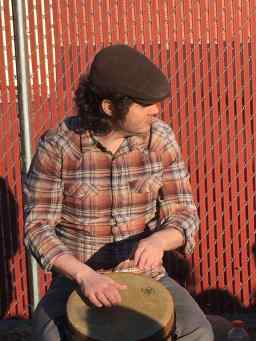 Photo: Curly-haired man wearing a hat in a plaid shirt playing an African drum.
