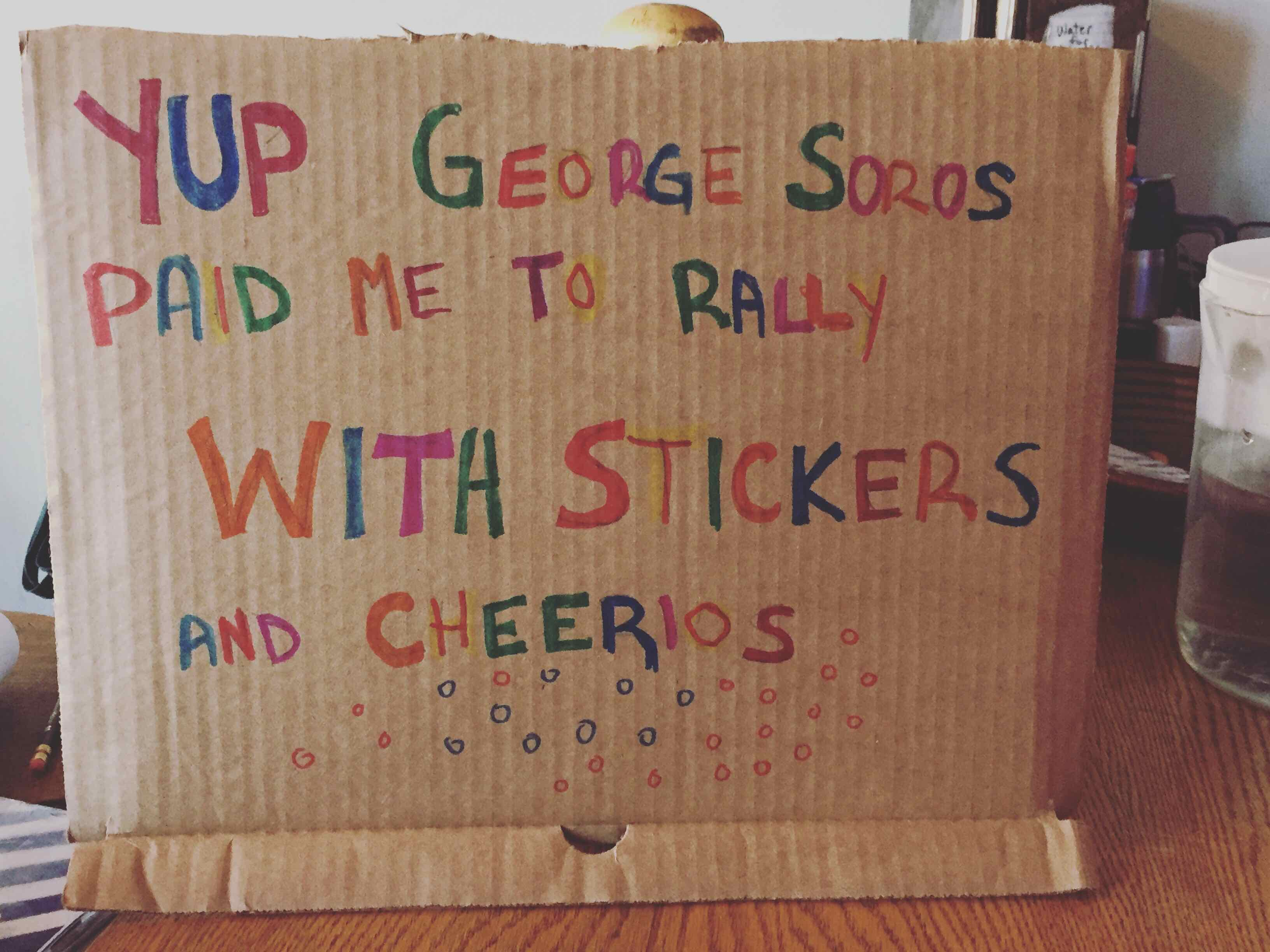 """Photo: Cardboard sign written in multi-colored marker reading """"Yup George Soros Paid Me to Rally with Stickers and Cheerios"""""""