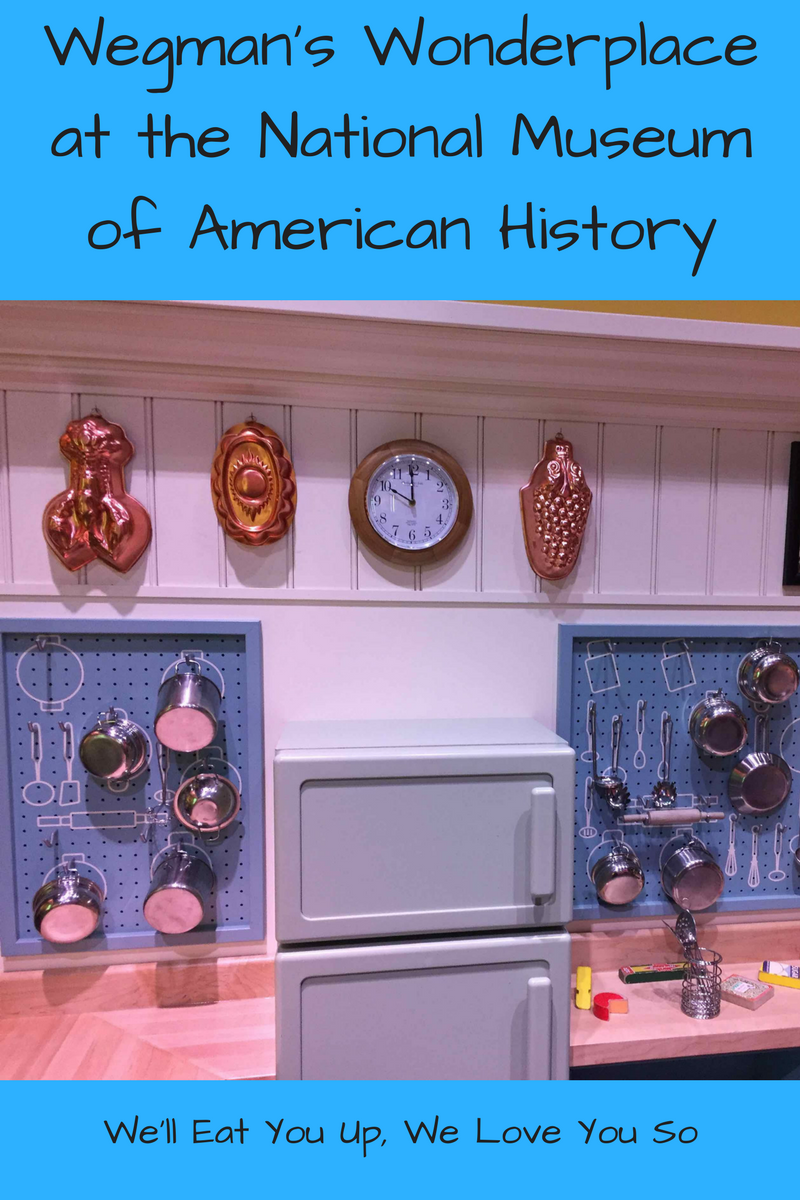 "Photo: Replica of Julia Child's kitchen as a toy kitchen for children with pots and pans hanging on the wall; Text: ""Wegman's Wonderplace at the National Museum of American History / We'll Eat You Up, We Love You So"""
