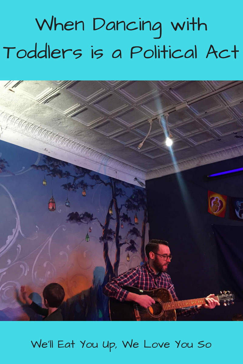 "Photo:  Man with a guitar in front of a mural and a kid behind him dancing. Text: ""When Dancing with Toddlers is a Political Act / We'll Eat You Up, We Love You So"""