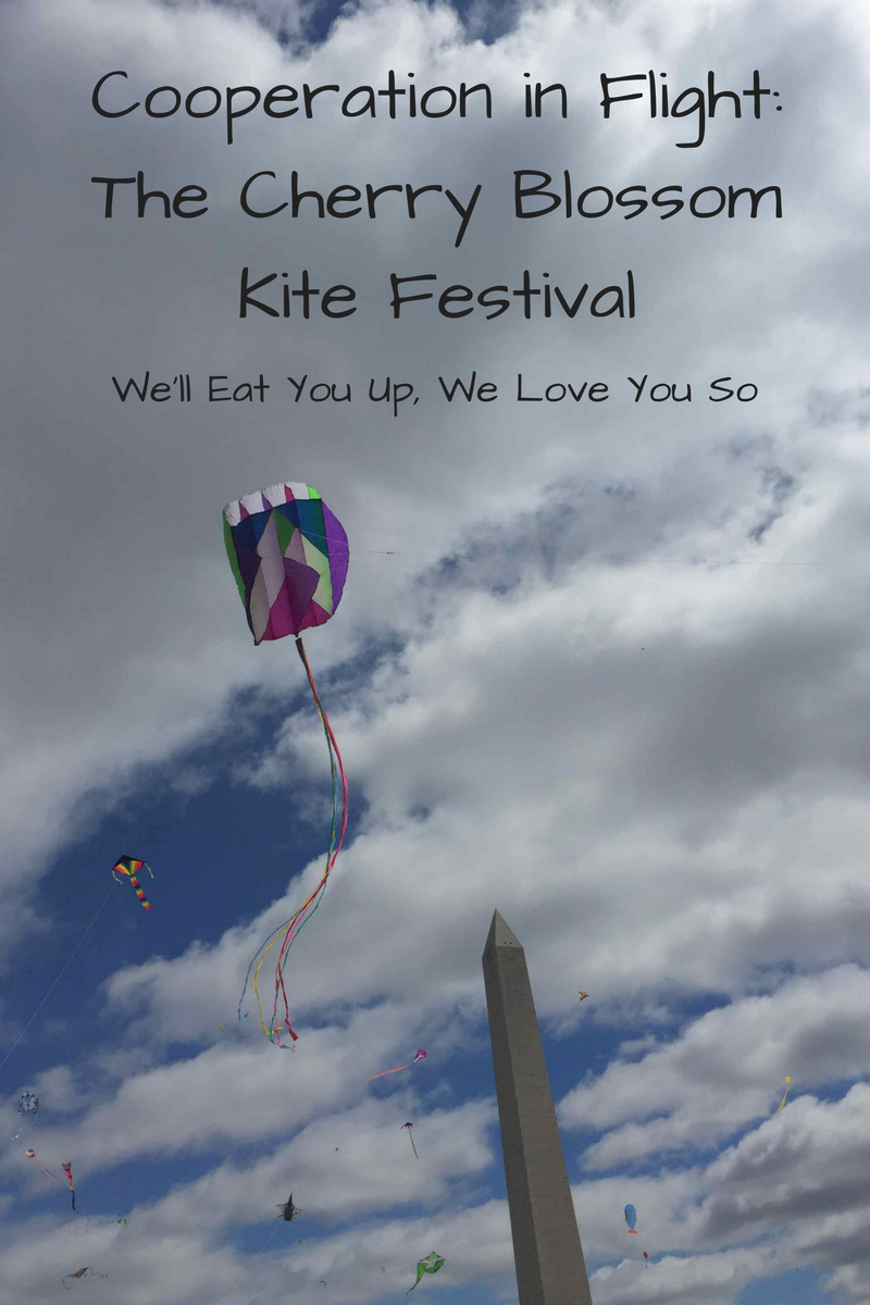"Text: ""Cooperation in Flight: The Cherry Blossom Kite Festival / We'll Eat You Up, We Love You So"" Photo: Multi-colored kite flying on a cloudy sky in front of the Washington Monument with other kites in the background"