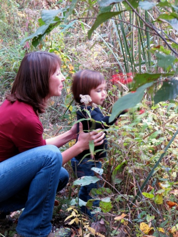 Photo: Woman kneeling and little girl looking at a variety of tall wildflowers
