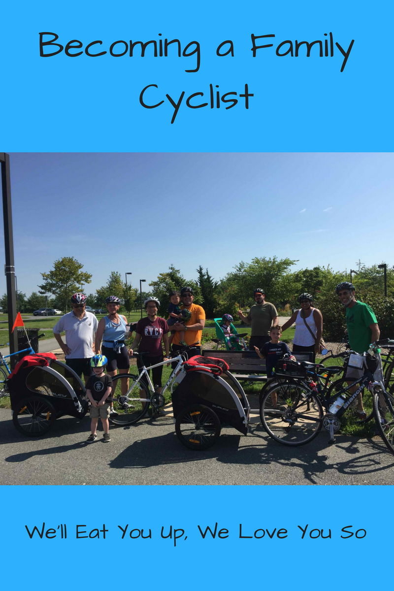 "Text: ""Becoming a Family Cyclist / We'll Eat You Up, We Love You So"" Photo: Bicyclists standing in a group with their bicyclists in a park"