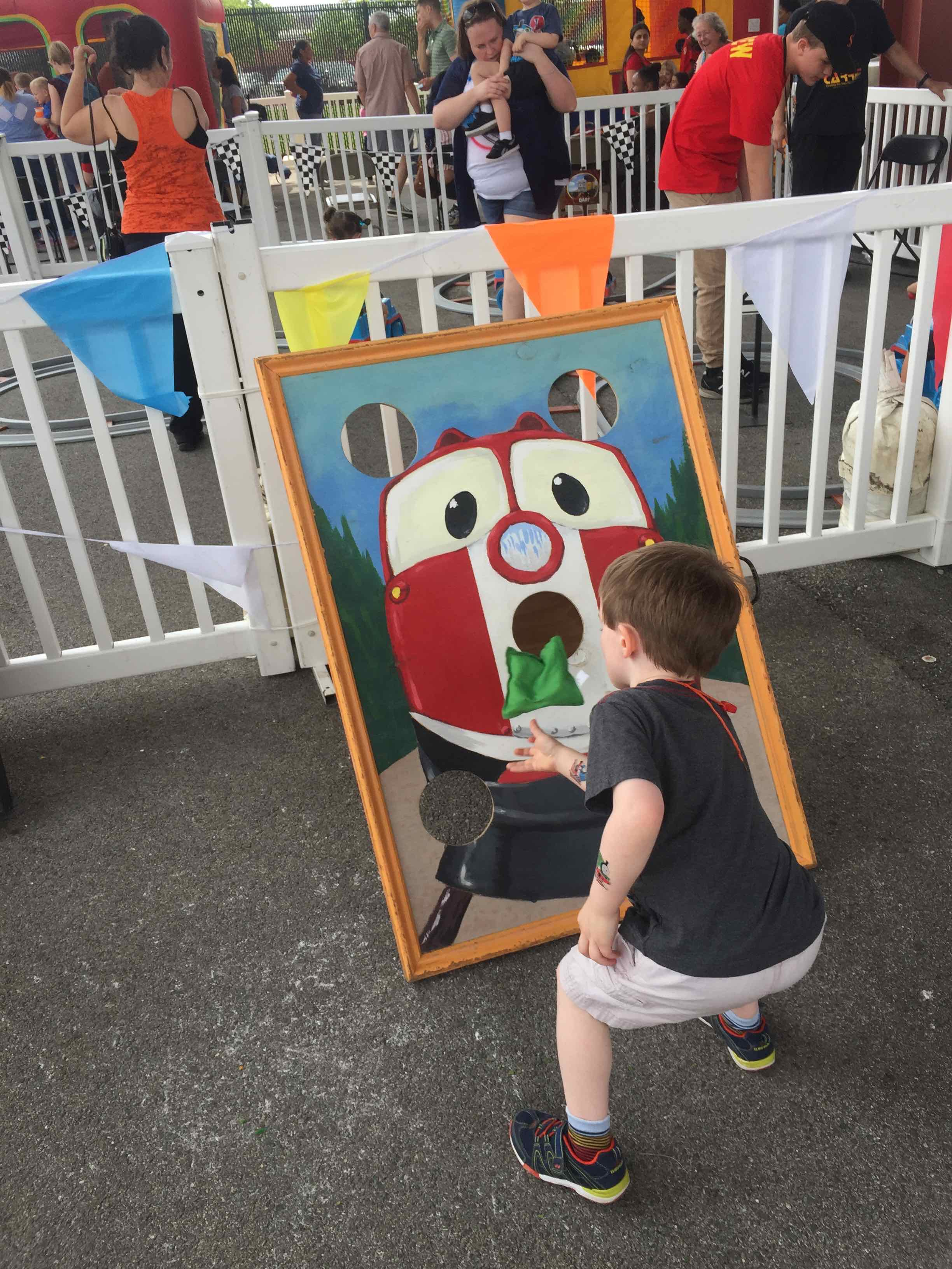 Photo: Child tossing a beanbag into a hole of a picture of a train.