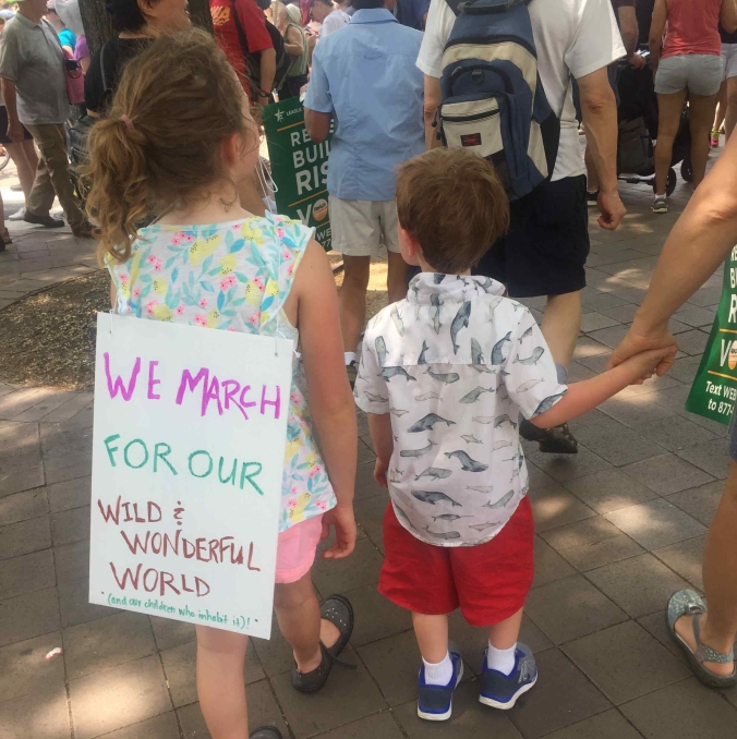 """Photo: Two kids walking, one with a sign saying """"We march for our wild and wonderful world."""""""
