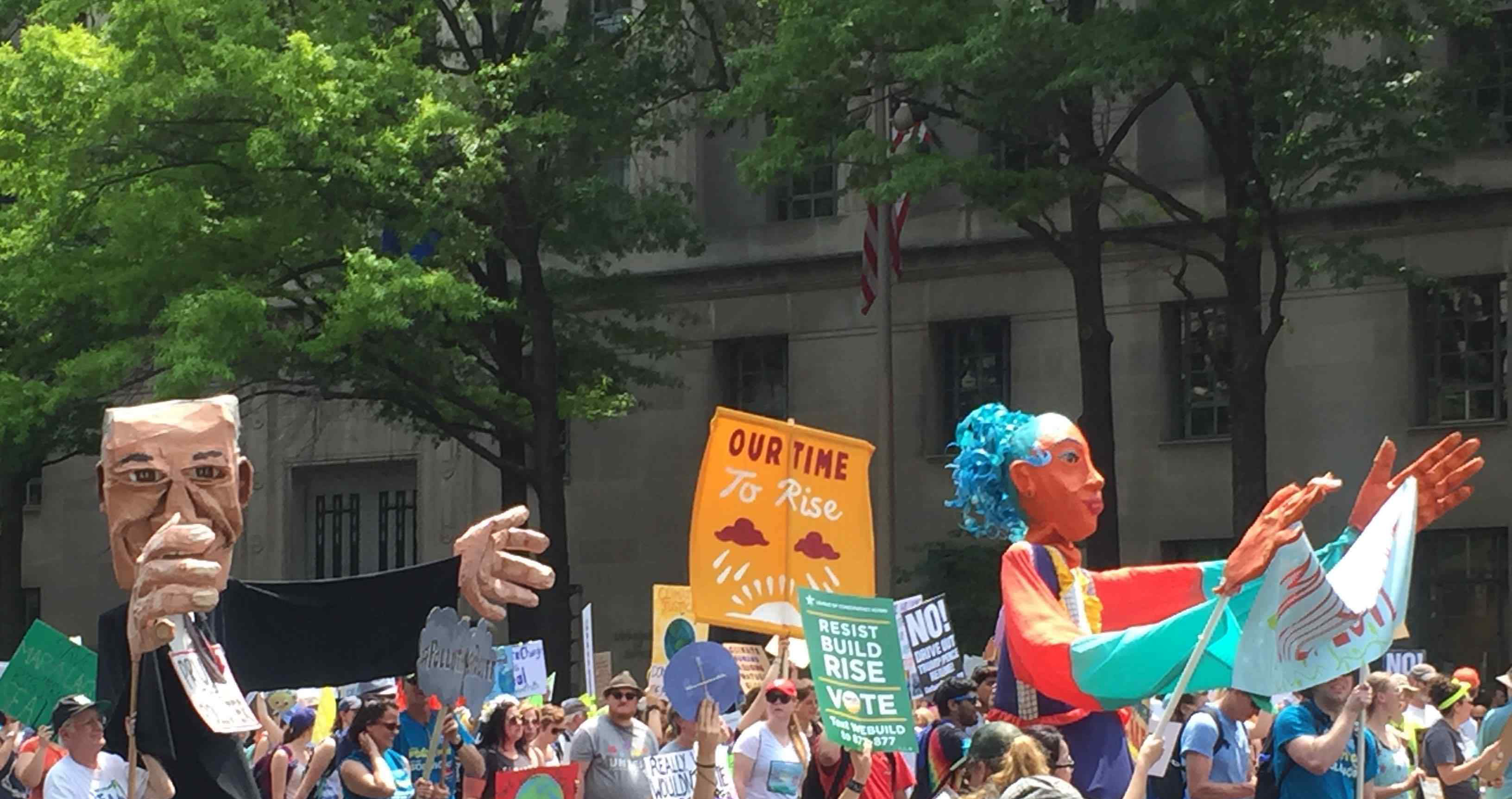 Photo: People marching in the People's Climate March with signs and paper mache puppets