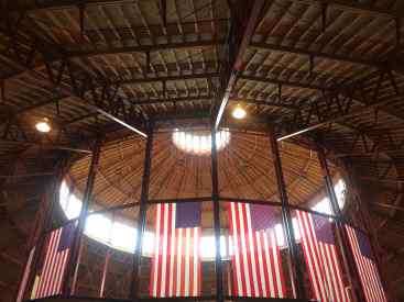 Photo: The roundhouse of a former train station looking up. Windows around the top letting in the sun, surrounded by American flags hanging from the ceiling.
